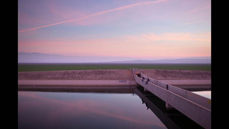 Kelly Goad and Casey Brown fish for striped bass in the California Aqueduct near Taft, Calif. on Wed. Feb 12. Beyond them are fields irrigated from the aqueduct, which conveys water from the Delta to Southern California.
