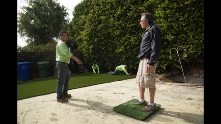 Waterless Turf owner Vic Watterson, right, talks to Jose Sanchez while they install an artificial lawn at a home in Santa Monica, Calif. on Tuesday Feb 11. Watterson estimates his call volume 'has increased around 30 percent' in 2014 due to drought and concerns about water rationing.